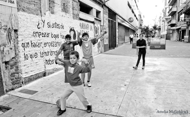 kids playing footbal in the streets uruguay montevideo black and white street photography