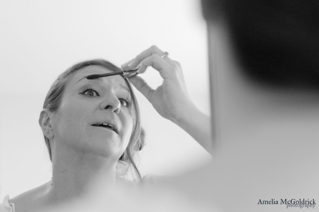 finishing touches on brides makeup mirror reflection black and white photography wedding day