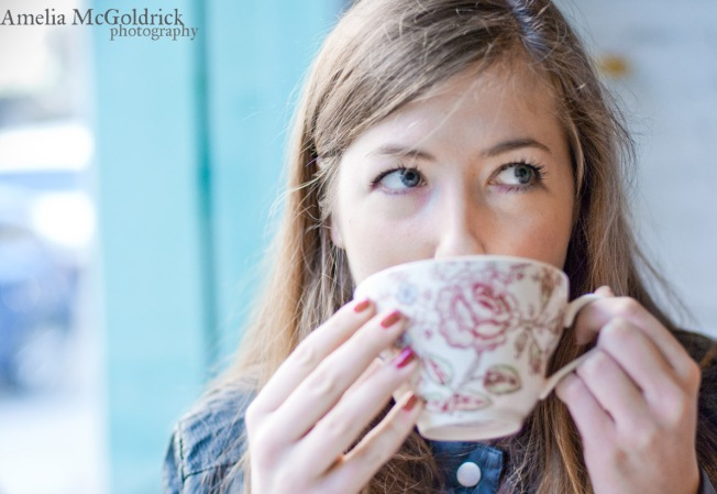 pretty girls sips chai tea from a flowered porcelain tea cup