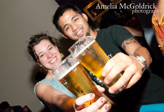 beer glasses and cheers with smiling couple
