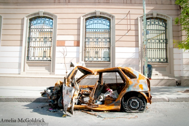 destroyed burned out car sits abandoned on the streets of Almagro Buenos Aires Argentina