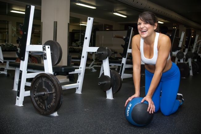 A fit woman poses with a medicine ball in a gym, Toronto Ontario