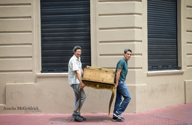 two men carry a vintage table through the streets of San Telmo, Buenos Aires, Argentina